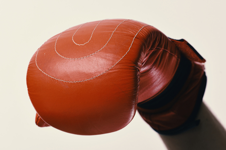 Sports and competition concept. Leather box equipment on white background, defocused. Boxing glove on male hand, close up.