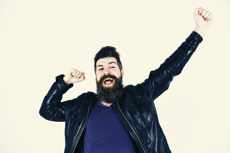 Menswear and fashion concept. Hipster looks cheerful while posing in stylish outfit. Man with beard and mustache on smiling face stretching arms. Macho wears leather jacket, white background.