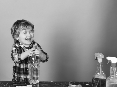 Cleaning activities concept. Kid with laughing face holds spray on table. Boy in checkered shirt on blue background. Child near wooden table with cleaning supplies on. Stock Photo
