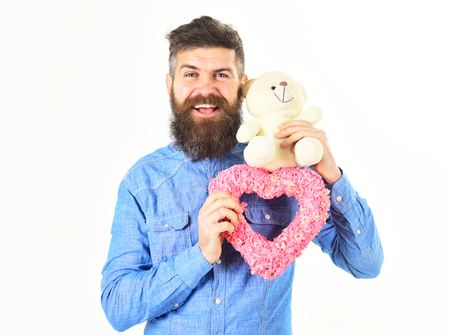 bearded macho man, brutal caucasian hipster with moustache with pink valentines heart on white background Stock Photo