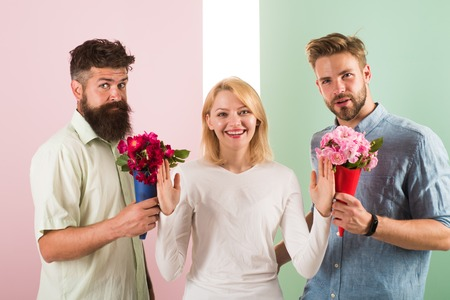 Men competitors with bouquets flowers try conquer girl. Girl smiling reject gifts. Out of relations. Feminism concept. Woman smiling reject both male partners. Girl popular receive lot men attention.