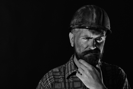 Worker with brutal image wears dirty helmet and plaid shirt. Builder or mine worker with thick beard. Construction and mining concept. Man with thoughtful face isolated on black background, copy space. Stock Photo