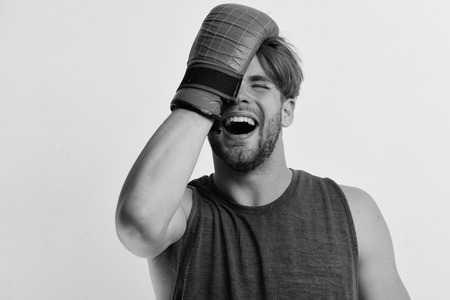 Boxer makes hits and punches as training. Man with bristle and laughing face wears boxing gloves. Sports and competition concept. Athlete with leather box equipment isolated on grey background.