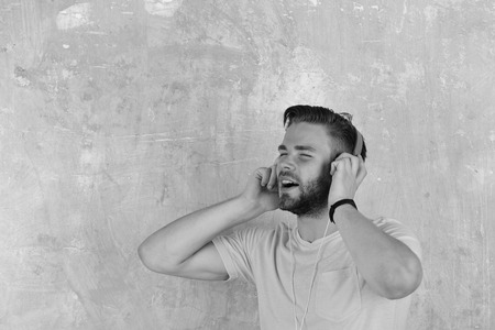 European man have fun time. American handsome bearded guy with headphones. Blue eyed stylish hipster with smartphone. Musical lifestyle. Cheerful dj listening songs via earphones.