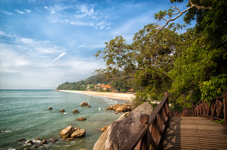 Stunning nature of Kuantan. Best Kuantan beach resorts famous for pristine nature. Coastline with tropic nature plants sand beaches. Bridge or wooden pier at sea lagoon with rocks and waves