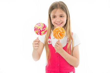 Hard choice. Cheerful little girl holding lollipops in her hands and smiling while standing isolated on white. Girl can not decide which lollipop she wants. Sweets addicted kid wants all candies 写真素材