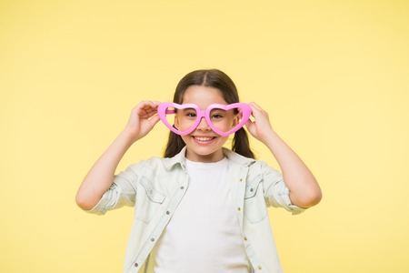 Happy child wear heart shaped glasses on yellow background. Little girl smile in fashion accessory. Summer fashion look. Funky style beauty. Young and confident. Valentines day. I love you