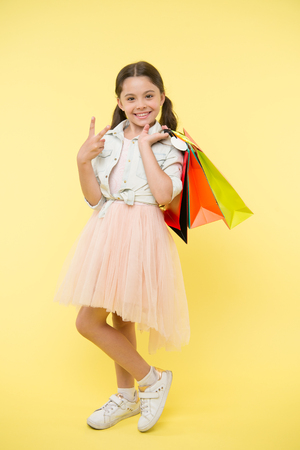 Big sale on black friday. Happy girl hold shopping bags on yellow background. Child smile with victory hand gesture and paper bags. Little shopaholic smiling in fashion wear. Having fun on shopping.