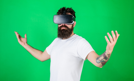 Superiority concept. Hipster on serious face raising hands while enjoy superiority in virtual reality. Man with beard in VR glasses, green background. Guy with head mounted display interact in VR.