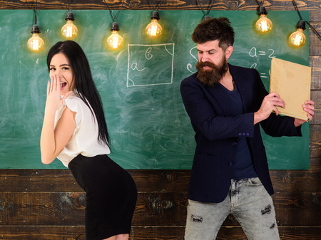Schoolmaster punishes student with slapping on her with book. Teacher spanking girl in classroom. Man with beard slapping student, chalkboard on background. Role game concept