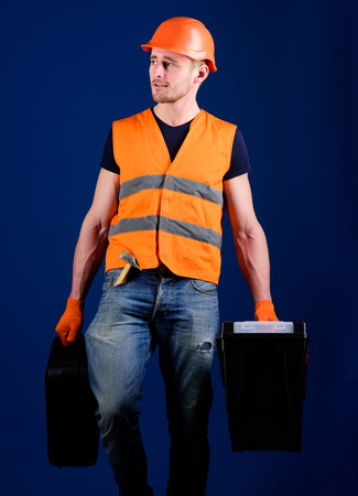 Man in helmet, hard hat holds toolbox and suitcase with tools, blue background. Professional repairman concept. Handyman, repairman on dreamy face goes and carries bags with professional equipment.