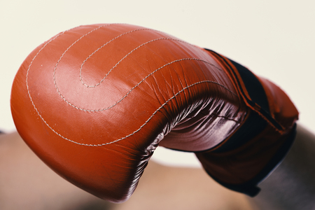 Boxer demonstrates red leather glove in close up. Athlete with box equipment isolated on white background. Sports and competition concept. Man shows muscle wearing boxing gloves. Stock Photo