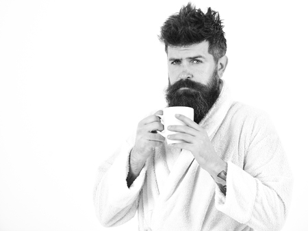 Morning rituals concept. Macho sleepy with strict face drinks coffee in morning, copy space. Man with beard and disheveled hair stands in bathrobe, holds mug with tea or coffee, white background. Banque d'images