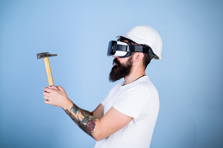 Hipster busy with renovation in virtual reality. Man with beard in VR glasses holds hammer, light blue background. Builder and renovation concept. Guy with HMD hammering virtual nail into VR surface. Stock Photo