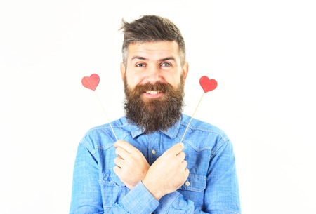 Hipster with paper red hearts and cheerful face. Happy bearded man holds symbols of love. Romantic mood. Full of love. Brutal man in love. Macho with beard smiles. Feelings, flirtation concept.