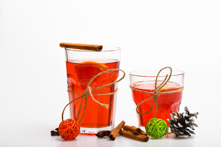 Glasses with mulled wine or hot drink tied with twine on white background, close up. Christmas drinks concept. Mulled wine or hot beverage in glasses with cinnamon sticks and fir cone. Stock Photo