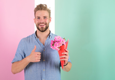Best choice. Man ready for date bring pink flowers. Boyfriend smiling holds bouquet waiting for date. Guy bring romantic pleasant gift waiting for her. Macho holds bouquet as romantic gift.