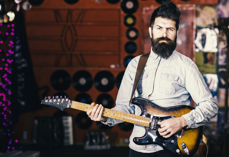 Talented musician, soloist, singer play guitar in music club on background. Musician with beard play electric guitar. Rock music concept. Man with strict face play guitar, singing song, play music. Stock Photo