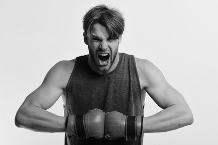 Man with bristle and furious face wears boxing gloves. Boxer makes hits and punches as training. Sports and competition concept. Athlete with leather box equipment isolated on white background. Фото со стока