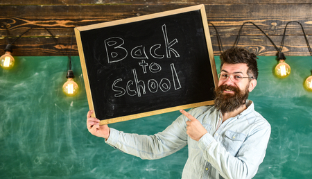 Teacher in eyeglasses holds blackboard with title back to school. Hiring teachers concept. Man with beard and mustache on happy face welcomes colleagues, chalkboard on background.