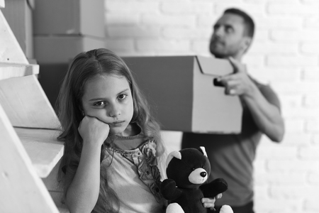 Daughter hugs teddy bear and father puts box into pile. Kid and guy move in or move out.