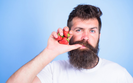 Fresh juice concept. Man drinks strawberry juice suck thumb as drink straw blue background. Hipster bearded holds strawberries fist as juice bottle. Man strict face enjoy fresh drink strawberry juice. Stock Photo