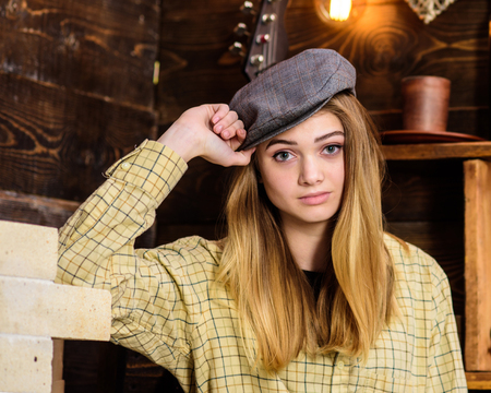 Girl in casual outfit with kepi in wooden vintage interior. Girl tomboy spend time in house of gamekeeper. Tomboy concept. Lady on calm face in plaid clothes looks cute and casual.