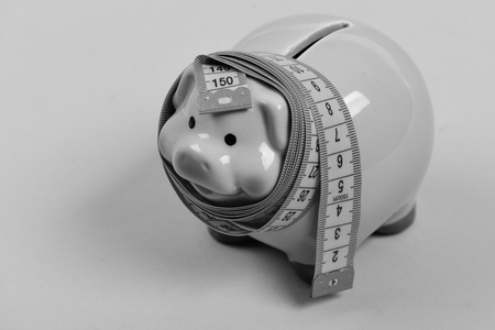 Budget and squeezed savings concept. Investments and metering or counting idea. Piggy bank tied with measuring tape. Ceramic toy pig with blue flexible ruler on blue background.