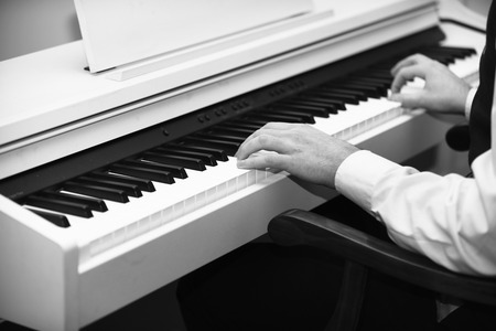 Piano player concept. Male hands creating music on white piano background. Music performers hands with white cuffs playing piano. White piano with black keyboard and musicians hands.