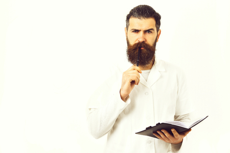 Medicine concept. Bearded man, long beard. Brutal caucasian doctor or unshaven hipster, postgraduate student holding notebook with pen in medical gown isolated on white studio background.