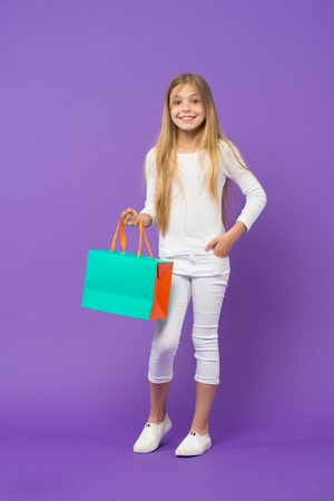 Girl wearing white jumper and trousers isolated on purple background. Kid with cheerful face holding paper bag. Child surprised by gift, birthday concept. Girl with big smile doing shopping
