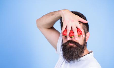 イチゴの盲目。ひげを生やしたヒップスターは、目の前にイチゴで手をつないでいます。私の心にイチゴ。ベリーに阻まれた男の一見。男はイチゴブルーの背景以外の何かを見ることができない。 写真素材 - 104378788