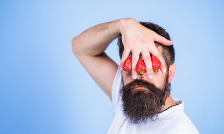 Blind of strawberry. Man bearded hipster hold hand with strawberries in front of eyes. Strawberry on my mind. Glance of man blocked by berries. Man can not see anything but strawberry blue background. 写真素材