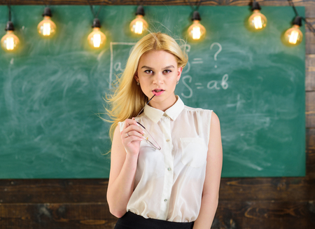 Sexy teacher concept. Woman with long hair in white blouse stands in classroom. Teacher with glasses and waving hair looks sexy. Lady strict teacher on dreamy face stands in front of chalkboard.