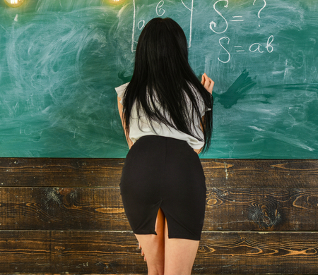 Teacher of mathematics writing on chalkboard, rear view. Lady sexy teacher in short skirt with slit explaining formula. Sexy teacher concept. Woman with nice buttocks teaching mathematics.