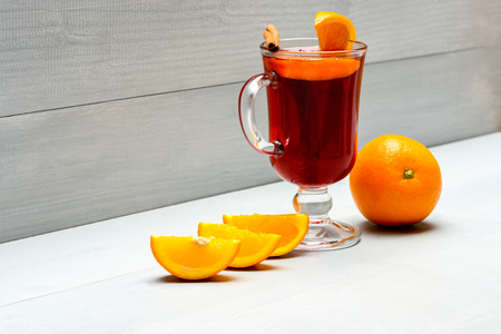 Glass with mulled wine or hot cider near juicy orange fruit on white wooden background. Drink or beverage with orange and cinnamon. Mulled wine near slices of orange. Cocktail and bar concept.