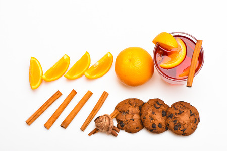 Mulled wine near slices of orange.Drink or beverage with orange and cinnamon. Cocktail and bar concept. Glass with mulled wine or hot cider near orange slices and cookies on white background. Stock Photo