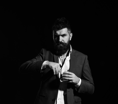 Businessman with serious face in suit on black background ready to drink cognac. Man holding glass of whiskey or bourbon and bottle. Partying and drinking concept. Sommelier with beard tasting alcohol