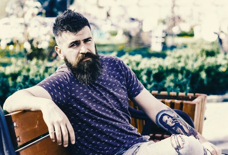 Rest and relax concept. Bearded man with fresh haircut relaxing, urban background. Hipster enjoy sunny day in park. Man with beard and mustache on strict face sits on bench in park.