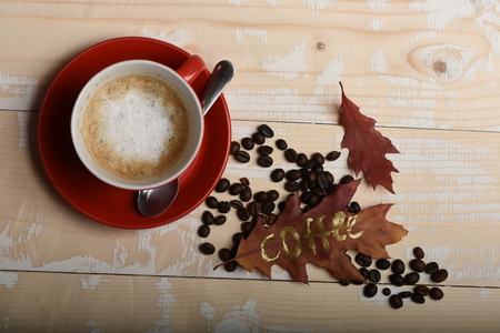 Autumn mood concept. Warm and cozy autumn picture. Cup hot cappuccino coffee on wooden table with autumn leaves and coffee beans, top view.