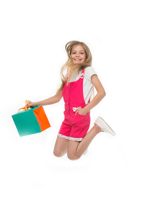 Finally bought it. Girl cute teenager carries shopping bag while jumping. Sale benefits. Kid bought clothing summer sale. Seasonal sale concept. Girls absolutely fond of shopping Stock Photo