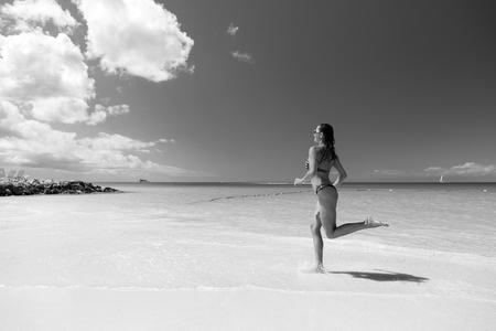 Woman running on sea beach with white sand