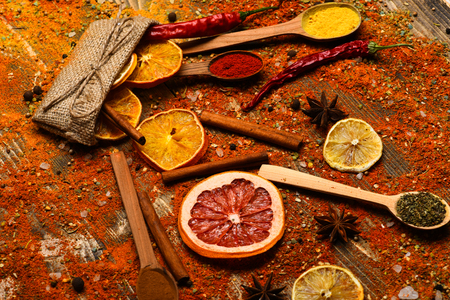 Spoons filled with cinnamon, grinded red pepper and curcuma powder and kitchen herbs scattered on table. Spices concept. Spices scattered all over wooden surface. Spoons with spices on wooden texture. 免版税图像