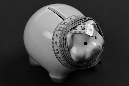 Measuring tape wrapped around piggy bank or money box on black background. Savings and financian diet concept Stock Photo