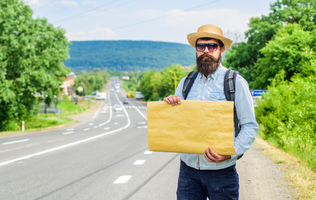 Short general directions. Man bearded hitchhiker stand at edge of road with blank paper sign, copy space. Benefits using sign with name destination. Cardboard sign with indication where you want go.