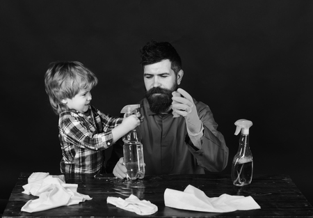 Man and child with concentrated face on black background. Guy with beard and mustache in rubber gloves at table. Kid holds cleaning spray and father holds sponge. Cleaning activities concept. Stock Photo