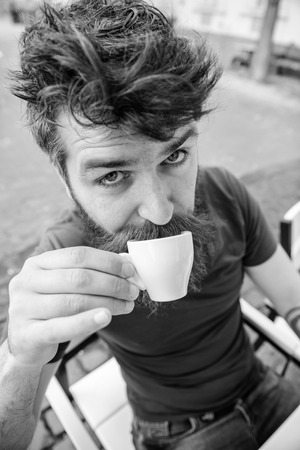Hipster on surprised face drinking coffee outdoor. Man with beard and mustache holds cup of coffee while relaxing at cafe terrace. Coffee break concept. Guy having rest with espresso coffee. Imagens