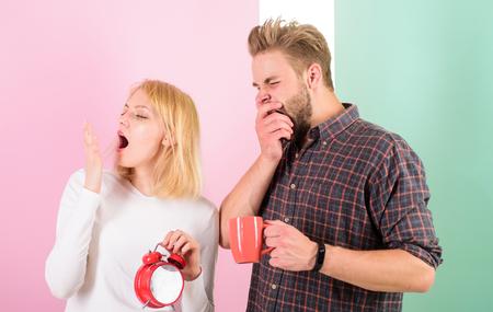 Too early awakening. Couple sleep not enough time. Family drink morning coffee yawning faces. Hate morning awakening. Harmful habit to oversleep. Couple oversleep awakening hold alarm clock Banco de Imagens
