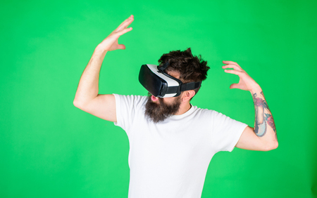 Hipster with inspired expression exploring VR with modern gadget. VR gadget concept. Guy with head mounted display interact in virtual reality. Man with beard in VR glasses, green background.