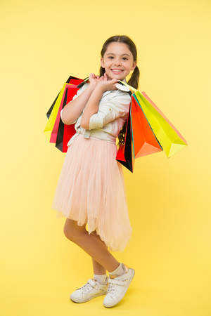 Tips to save money on back to school supplies and clothing. Back to school season teach budgeting basics. Girl carries shopping bags. Prepare for school season buy supplies clothes in advance Stock Photo
